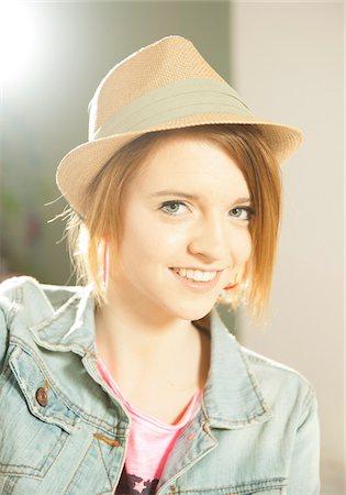 Head and shoulders portrait of teenage girl wearing hat in studio. Stock Photo - Premium Royalty-Free, Code: 600-06553546