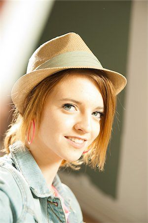 Head and shoulders portrait of teenage girl wearing hat in studio. Stock Photo - Premium Royalty-Free, Code: 600-06553548