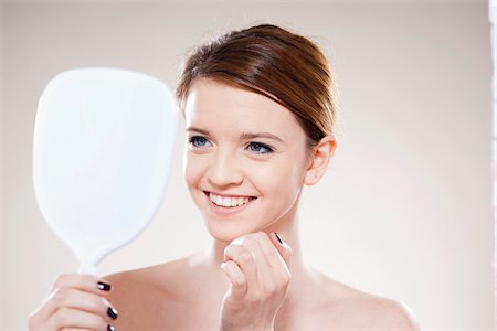 Head and Shoulders Portrait of Teenage Girl Looking in Mirror in Studio Stock Photo - Premium Royalty-Free, Code: 600-06570928