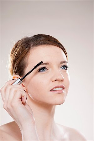 Head and Shoulders Portrait of Teenage Girl Putting on Mascara in Studio Stock Photo - Premium Royalty-Free, Code: 600-06570932