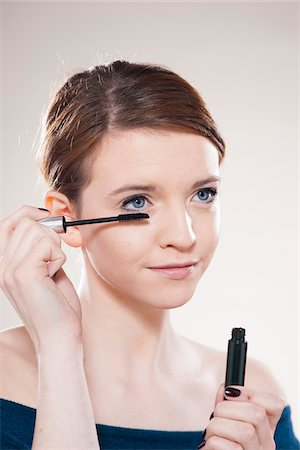 Head and Shoulders Portrait of Teenage Girl Putting on Mascara in Studio Stock Photo - Premium Royalty-Free, Code: 600-06570933