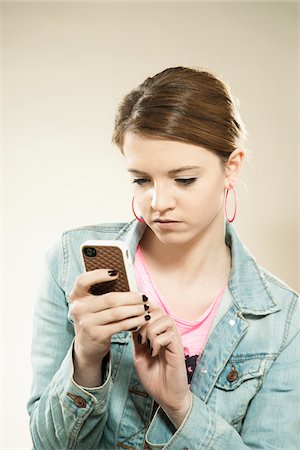 Portrait of Teenage Girl Reading Text Message on a Cell Phone in Studio Stock Photo - Premium Royalty-Free, Code: 600-06570946