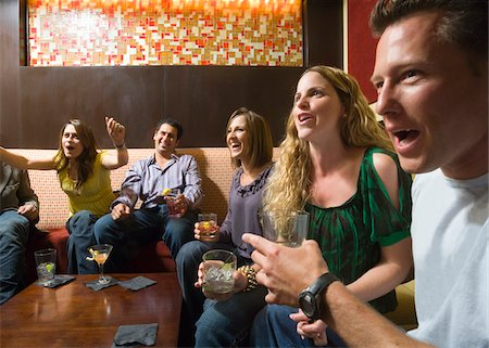 Men and women socializing in a bar in the city. Group of festive, smiling people celebrating with drinks. California USA Stock Photo - Premium Royalty-Free, Code: 600-06571137
