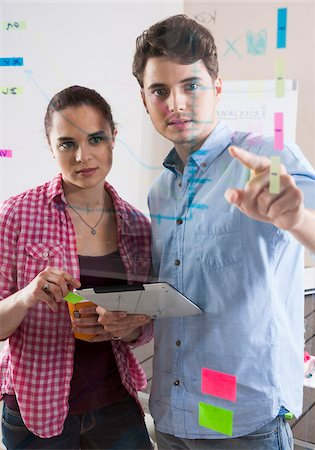 drawing computer - Young Man and Young Woman Working in an Office, Looking Through Glass Board, Germany Stock Photo - Premium Royalty-Free, Code: 600-06620947