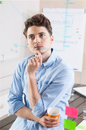 Young Man Working in an Office, Looking Through Glass Board, Germany Stock Photo - Premium Royalty-Free, Code: 600-06620955