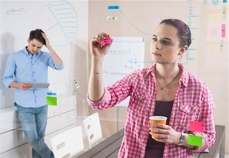 drawing computer - Young Man and Young Woman Working in an Office, Looking Through Glass Board, Germany Stock Photo - Premium Royalty-Free, Code: 600-06620951