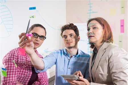 displaying - Business People Working in Office Looking at Plans Displayed on a Glass Board Stock Photo - Premium Royalty-Free, Code: 600-06620989