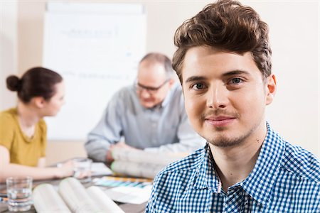 designer (female) - Portrait of Young Businessman with Colleagues Meeting in the Background Stock Photo - Premium Royalty-Free, Code: 600-06621001