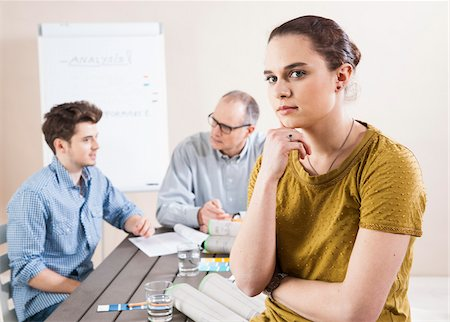 staff - Portrait of Young Businesswoman Leaning on Hand with Colleagues Meeting in the Background Stock Photo - Premium Royalty-Free, Code: 600-06621003