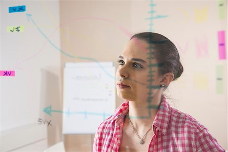 strategy - Young Businesswoman Working in Office Looking at Plans Displayed on a Glass Board Stock Photo - Premium Royalty-Free, Code: 600-06621019