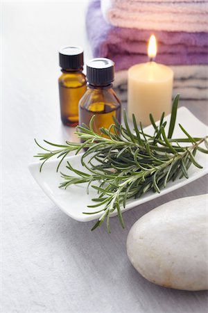 Sprig of rosemary, fresh herbs, candle, towel and bottles of essential oil for aromatherapy Stock Photo - Premium Royalty-Free, Code: 600-06674995