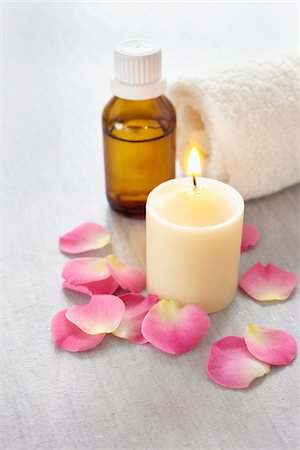 Rose petals, candle, rolled towel and a bottle of essential oil for aromatherapy Stock Photo - Premium Royalty-Free, Code: 600-06674990