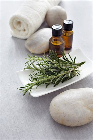 Sprig of rosemary, fresh herbs, a towel and bottles of essential oil for aromatherapy Stock Photo - Premium Royalty-Free, Code: 600-06674991