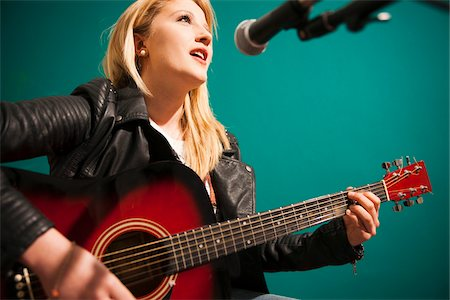 Woman Playing Acoustic Guitar and Singing in Studio Stock Photo - Premium Royalty-Free, Code: 600-06675134