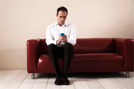 Mature Man Sitting on Sofa, Waiting and Looking at Cell Phone Stock Photo - Premium Royalty-Free, Code: 600-06679368