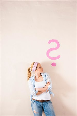 Studio Shot of Young Woman Leaning Against Wall with Question Mark Stock Photo - Premium Royalty-Free, Code: 600-06671776