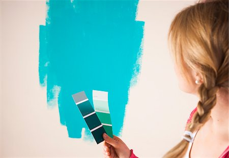 Studio Shot of Young Woman Holding Colour Swatches, Deciding Between Paint Colours Stock Photo - Premium Royalty-Free, Code: 600-06671787