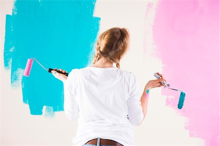 diy or home improvement - Studio Shot of Young Woman Holding Paint Rollers, Deciding Between Paint Colours Stock Photo - Premium Royalty-Free, Code: 600-06671795
