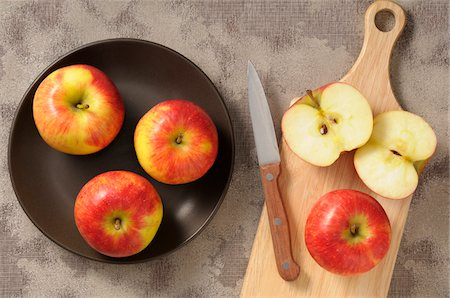 Overhead View of Apples on Plate and Cutting Board with Knife, One Cut in Half Stock Photo - Premium Royalty-Free, Code: 600-06671824