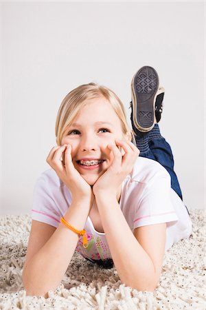 preteen  smile  one  alone - Portrait of Girl Leaning on Hands and Lying on Stomach in Studio Stock Photo - Premium Royalty-Free, Code: 600-06685164