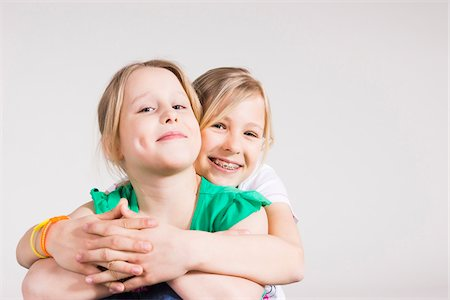 Portrait of Girl Hugging her Sister in Studio Stock Photo - Premium Royalty-Free, Code: 600-06685174