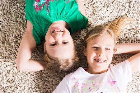 Overhead View of Girls lying on Carpet in Studio Stock Photo - Premium Royalty-Free, Code: 600-06685175