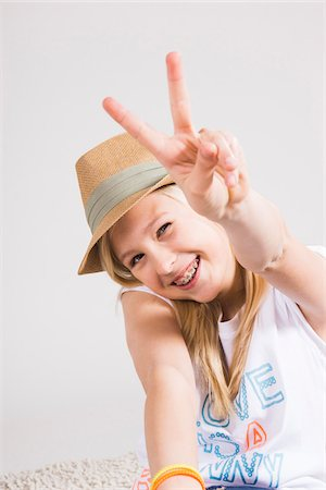 preteen  smile  one  alone - Portrait of Girl wearing Hat and making Peace Sign Gesture in Studio Stock Photo - Premium Royalty-Free, Code: 600-06685179