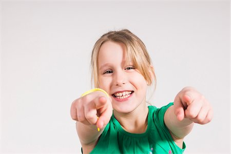 Head and Shoulders Portrait of Girl Pointing at Camera in Studio Stock Photo - Premium Royalty-Free, Code: 600-06685171