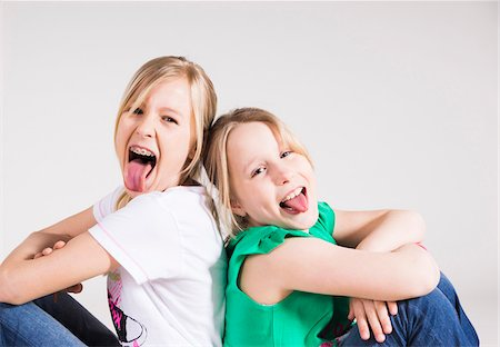 Portrait of Girls Sitting Back to Back and Sticking their Tongues Out Stock Photo - Premium Royalty-Free, Code: 600-06685173