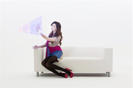 Young Businesswoman Sitting on Sofa using Digital Display, Studio Shot on White Background Stock Photo - Premium Royalty-Free, Code: 600-06685186