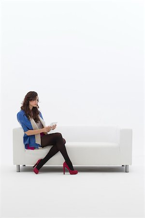 Young Businesswoman Sitting on Sofa using Tablet Computer, Studio Shot on White Background Stock Photo - Premium Royalty-Free, Code: 600-06685187