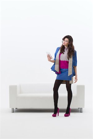 Young Businesswoman Standing in front of Sofa using Tablet Computer, Studio Shot on White Background Stock Photo - Premium Royalty-Free, Code: 600-06685188