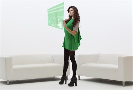 Young Businesswoman Standing in front of Sofa using Digital Display, Studio Shot on White Background Stock Photo - Premium Royalty-Free, Code: 600-06685194