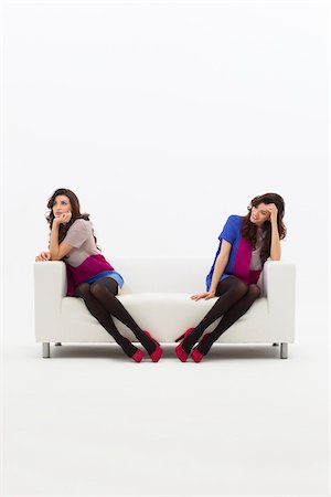 Multiple Image of Young Woman Sitting on Sofa, Studio Shot on White Background Stock Photo - Premium Royalty-Free, Code: 600-06685195
