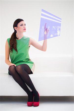 Young Businesswoman Sitting on Sofa using Digital Display, Studio Shot on White Background Stock Photo - Premium Royalty-Free, Code: 600-06685193