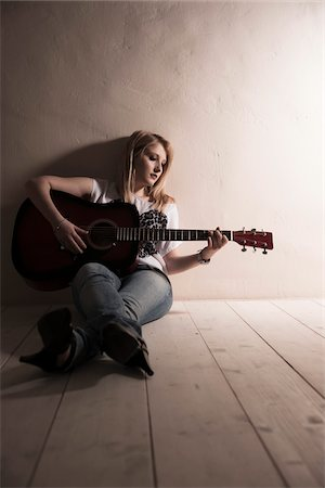 Young Woman Sitting on the Floor Playing Guitar in Studio Stock Photo - Premium Royalty-Free, Code: 600-06701796
