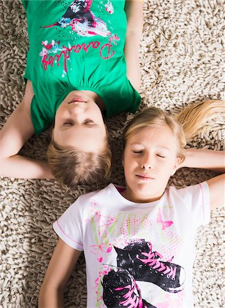 Young Girls Lying Down on a Carpet in Studio Stock Photo - Premium Royalty-Free, Code: 600-06701799