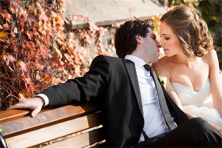 Portrait of Bride and Groom Kissing on Bench in Autumn, Toronto, Ontario, Canada Stock Photo - Premium Royalty-Free, Code: 600-06701878