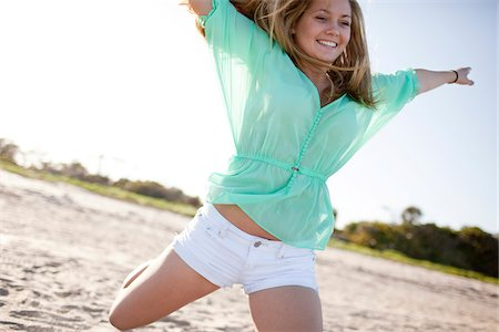 Young Woman Smiling and Jumping on Beach, Palm Beach Gardens, Palm Beach County, Florida, USA Stock Photo - Premium Royalty-Free, Code: 600-06701902