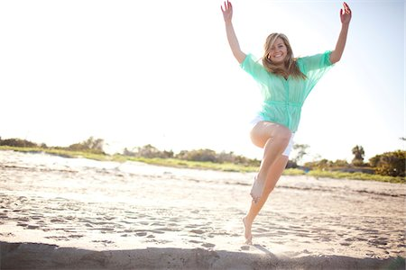 Young Woman Smiling and Jumping on Beach, Palm Beach Gardens, Palm Beach County, Florida, USA Stock Photo - Premium Royalty-Free, Code: 600-06701903