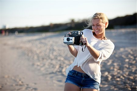 Young Woman Taking Pictures at Beach with Camera, Palm Beach Gardens, Palm Beach, Florida, USA Stock Photo - Premium Royalty-Free, Code: 600-06701914