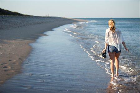 Young Woman Carrying Camera while Walking along Beach, Palm Beach Gardens, Palm Beach, Florida, USA Stock Photo - Premium Royalty-Free, Code: 600-06701915