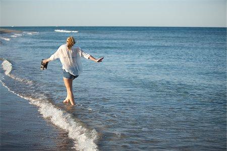 Young Woman Carrying Camera while Walking along Beach, Palm Beach Gardens, Palm Beach, Florida, USA Stock Photo - Premium Royalty-Free, Code: 600-06701916