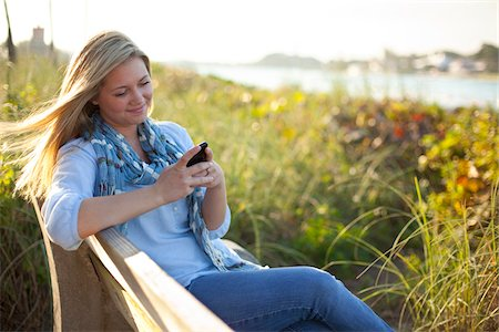 Young Woman Sitting on Bench at Beach, Texting on Cell Phone, Jupiter, Palm Beach County, Florida, USA Stock Photo - Premium Royalty-Free, Code: 600-06701918