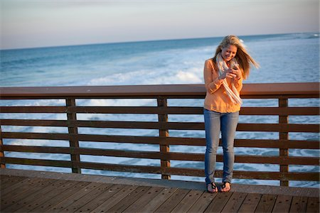 Young Woman Standing on Pier at Beach, Texting on Cell Phone, Jupiter, Palm Beach County, Florida, USA Stock Photo - Premium Royalty-Free, Code: 600-06701927