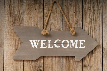 sign - Welcome Sign shaped like Arrow Hanging on Wall Stock Photo - Premium Royalty-Free, Code: 600-06702116