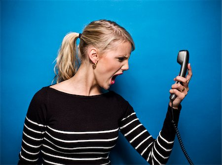 Young Woman Screaming at Telephone, Studio Shot Stock Photo - Premium Royalty-Free, Code: 600-06714008