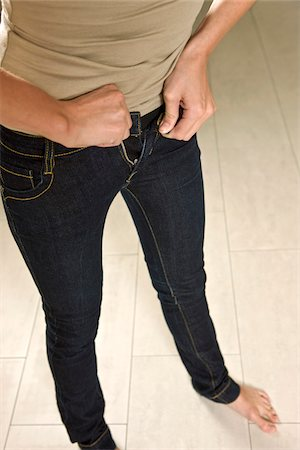 Young Woman Buttoning Tight Jeans Stock Photo - Premium Royalty-Free, Code: 600-06714001