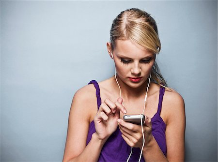 digital - Young Woman with MP3 Player, Studio Shot Stock Photo - Premium Royalty-Free, Code: 600-06714023