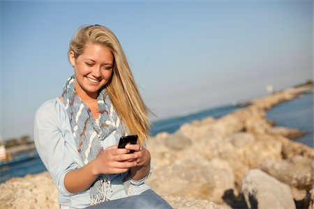 Young Woman Sitting on Rocks and Texting on Cell Phone at Beach, Jupiter, Palm Beach County, Florida, USA Stock Photo - Premium Royalty-Free, Code: 600-06732632